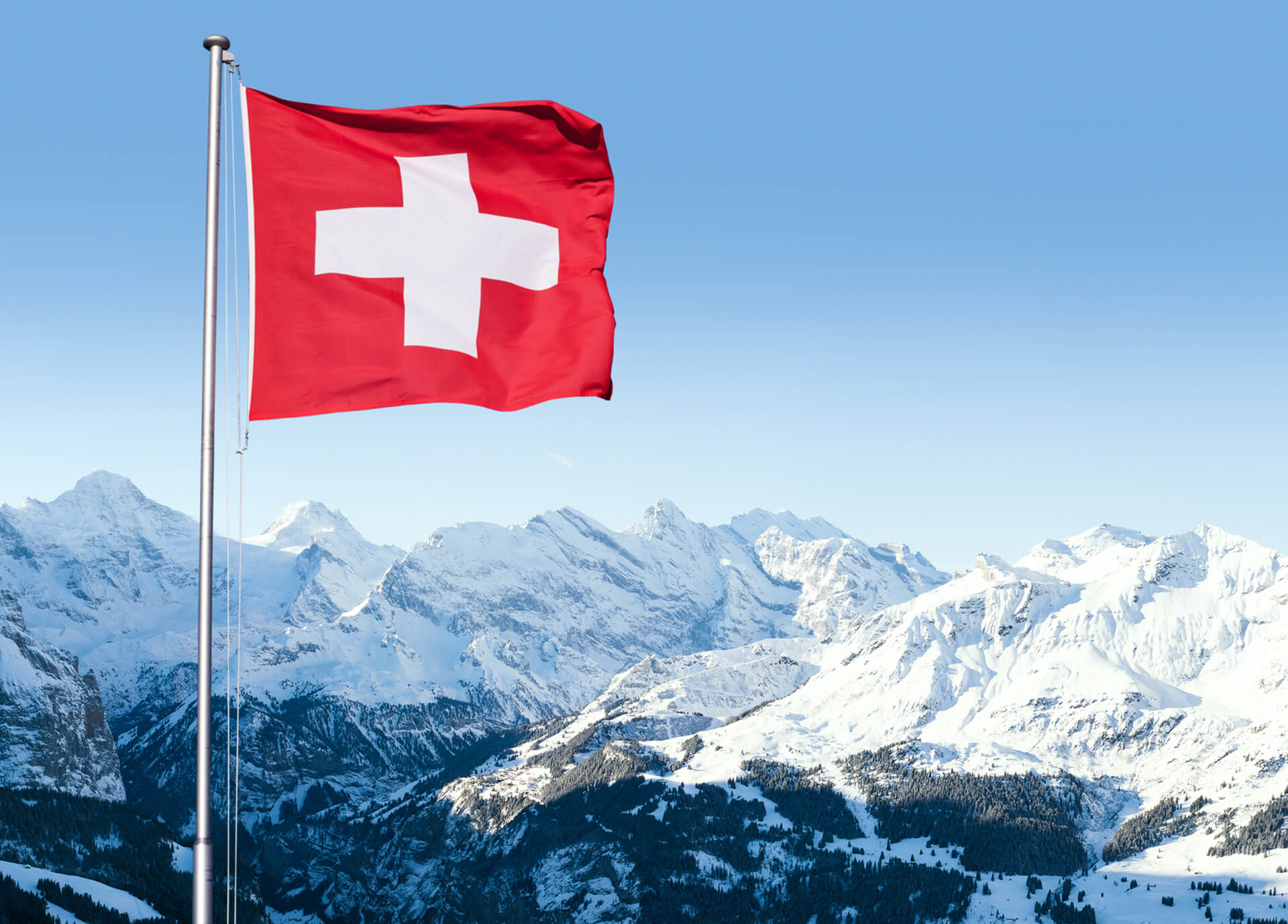 View over snowy Swiss mountains with swiss flag in foreground.